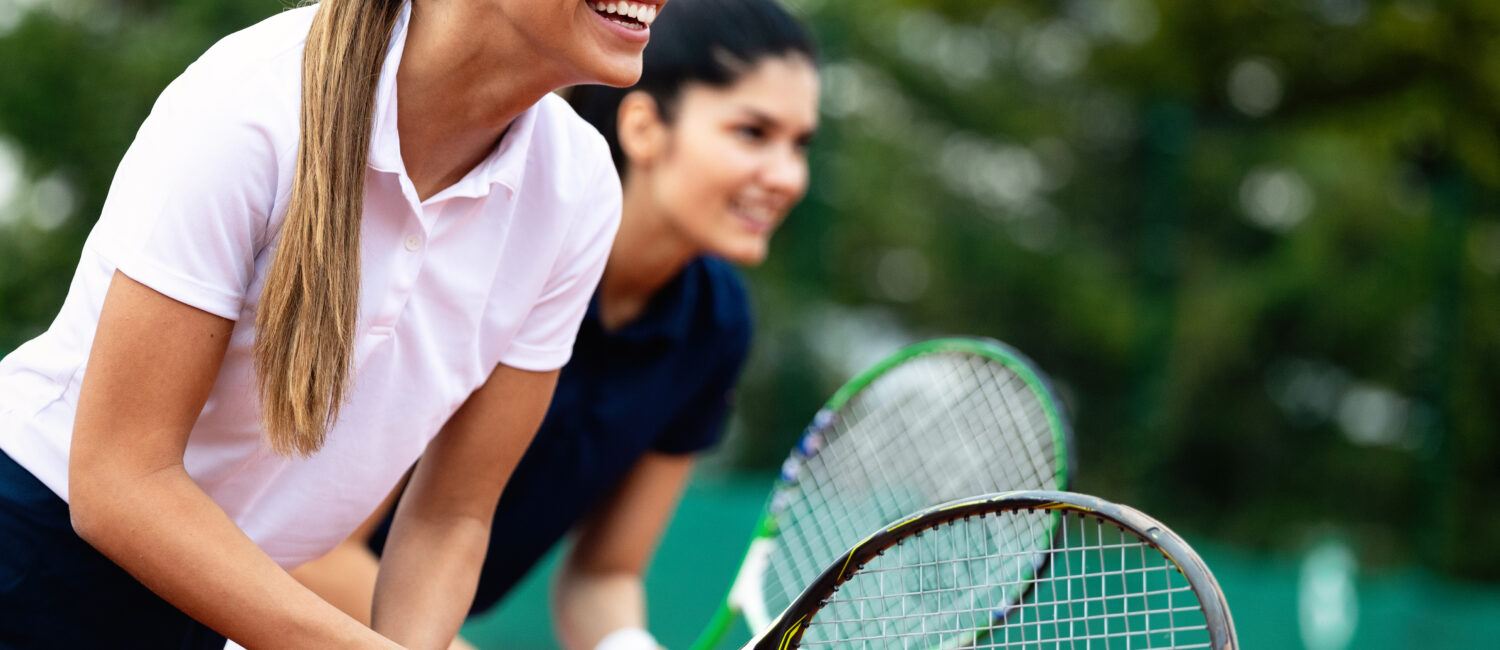 Happy fit people playing tennis together. Sport concept