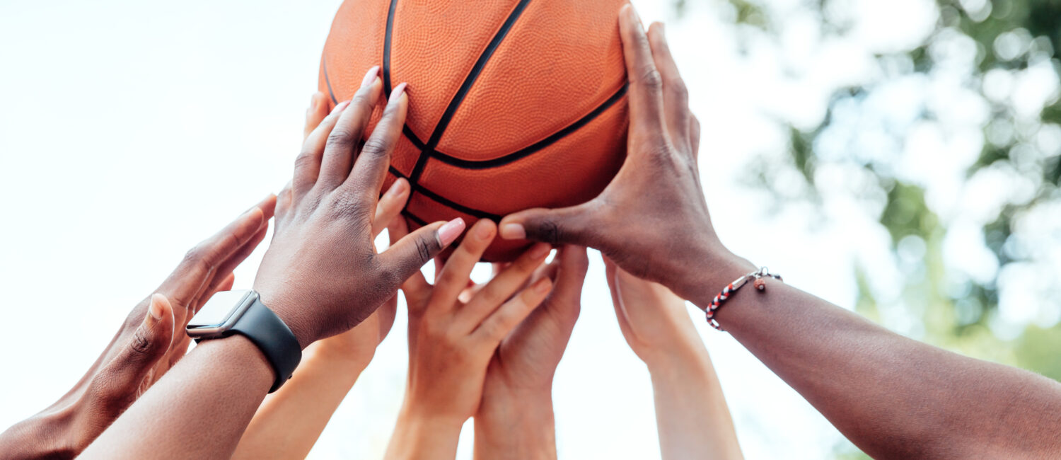 Close-up of multi-ethnic friends holding basketball above