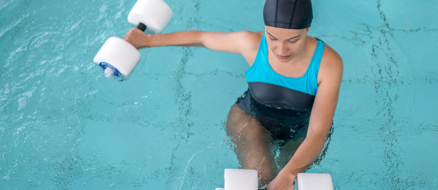 Young woman doing physiotherapy exercises in the water - healthcare and medicine concepts