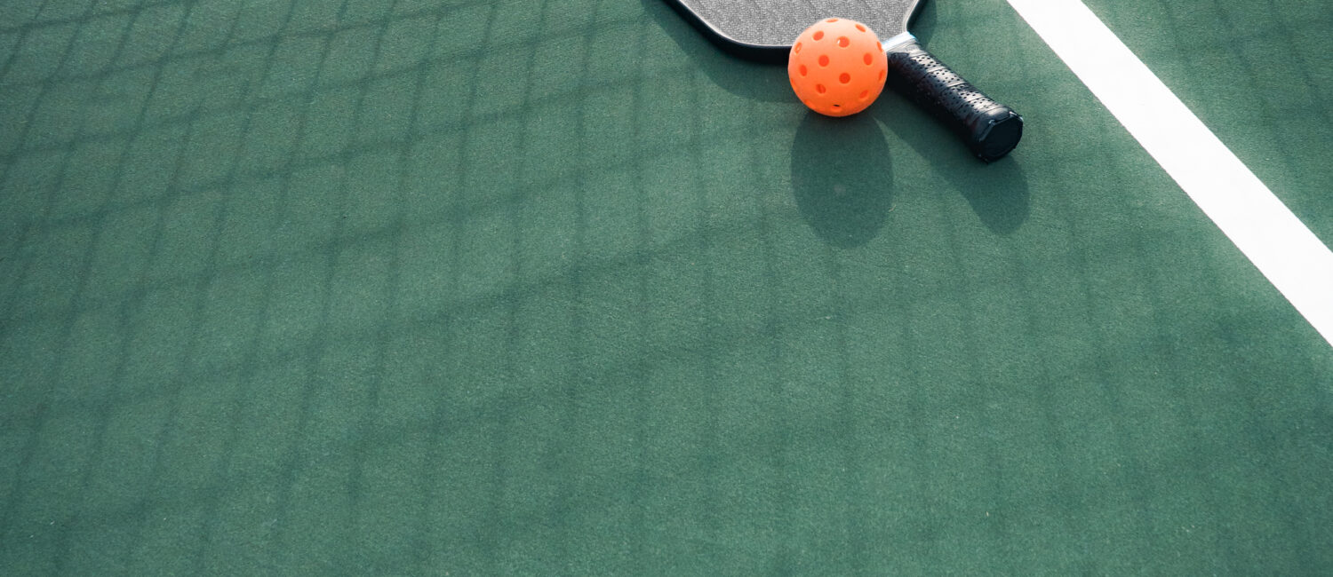 Pickleball and paddle on court