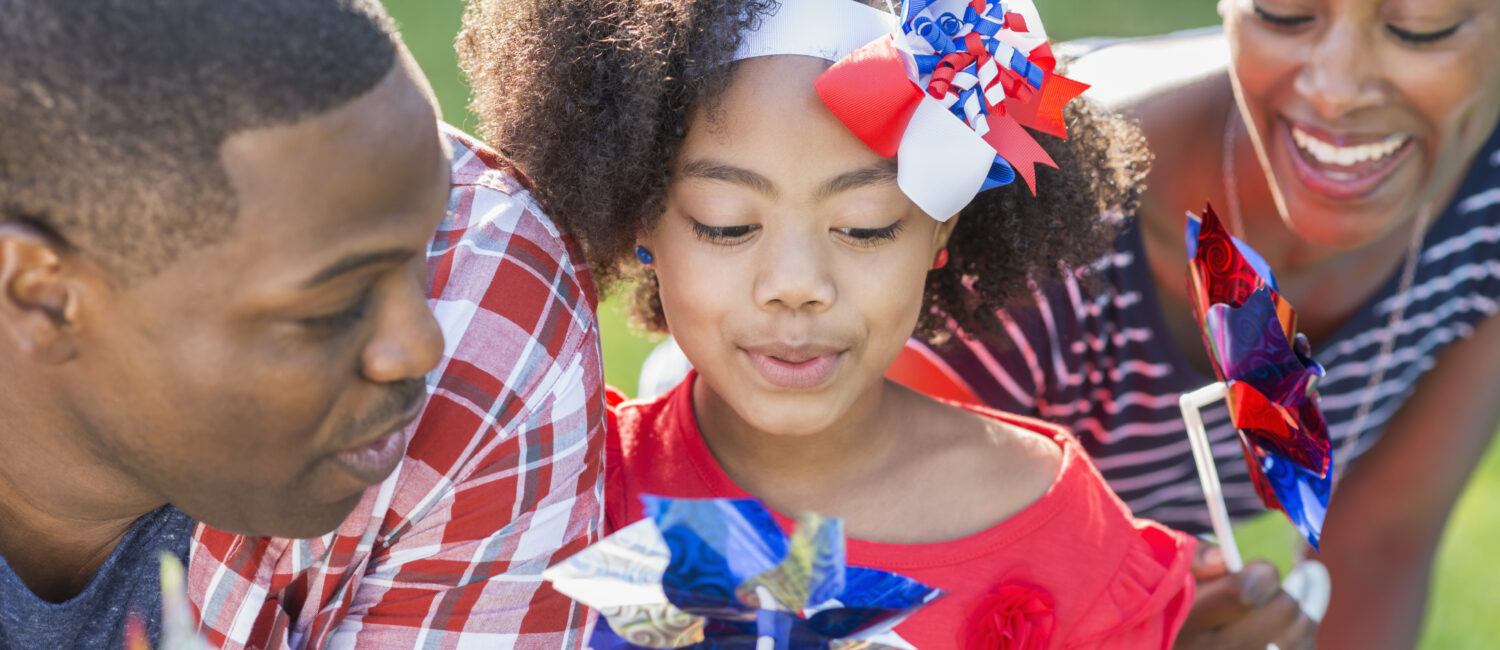 A mixed race African American family celebrating an American patriotic holiday, perhaps Memorial Day or July 4th. They are playing with red, white and blue pinwheels. The little girl in the middle, 7 years old, is part black, Asian and Hispanic.
