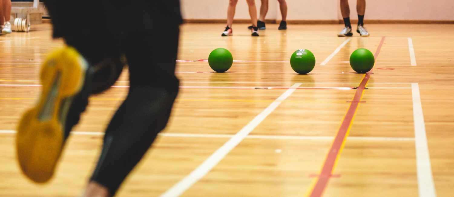 Individuals playing dodgeball in a gymnasium.