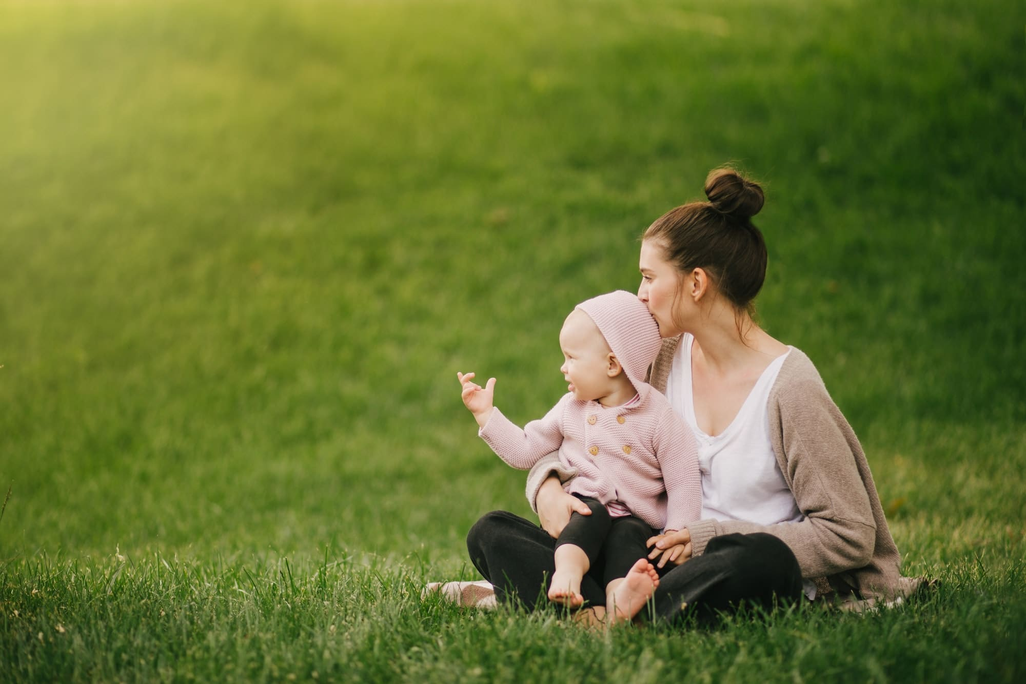 Young mother and her baby relaxing on green lawn.