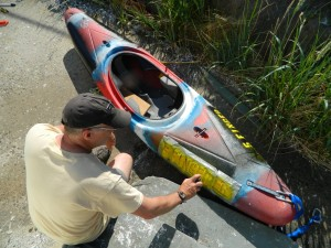 Paul Sharpe uses stencils and spray paint to put ID on kayak that will house hydrophone.