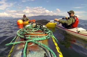 Fred and Paul Sharpe in kayaks deploying hydrophone at Five Finger Lighthouse in SE Alaska.
