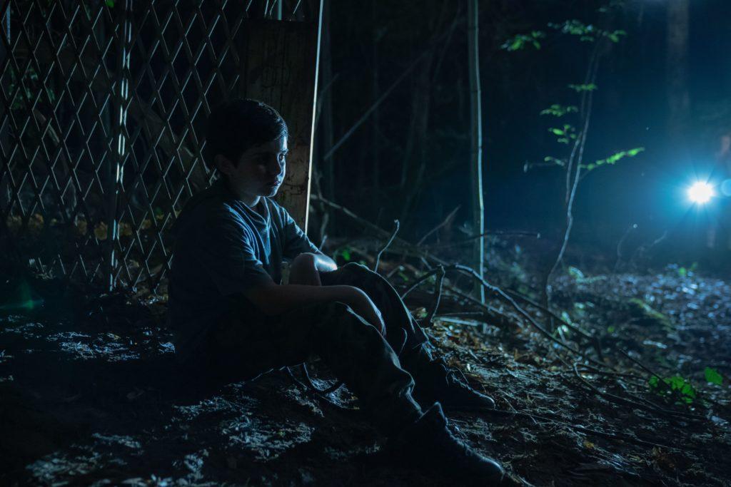 boy-sitting-against-a-fence-at-night