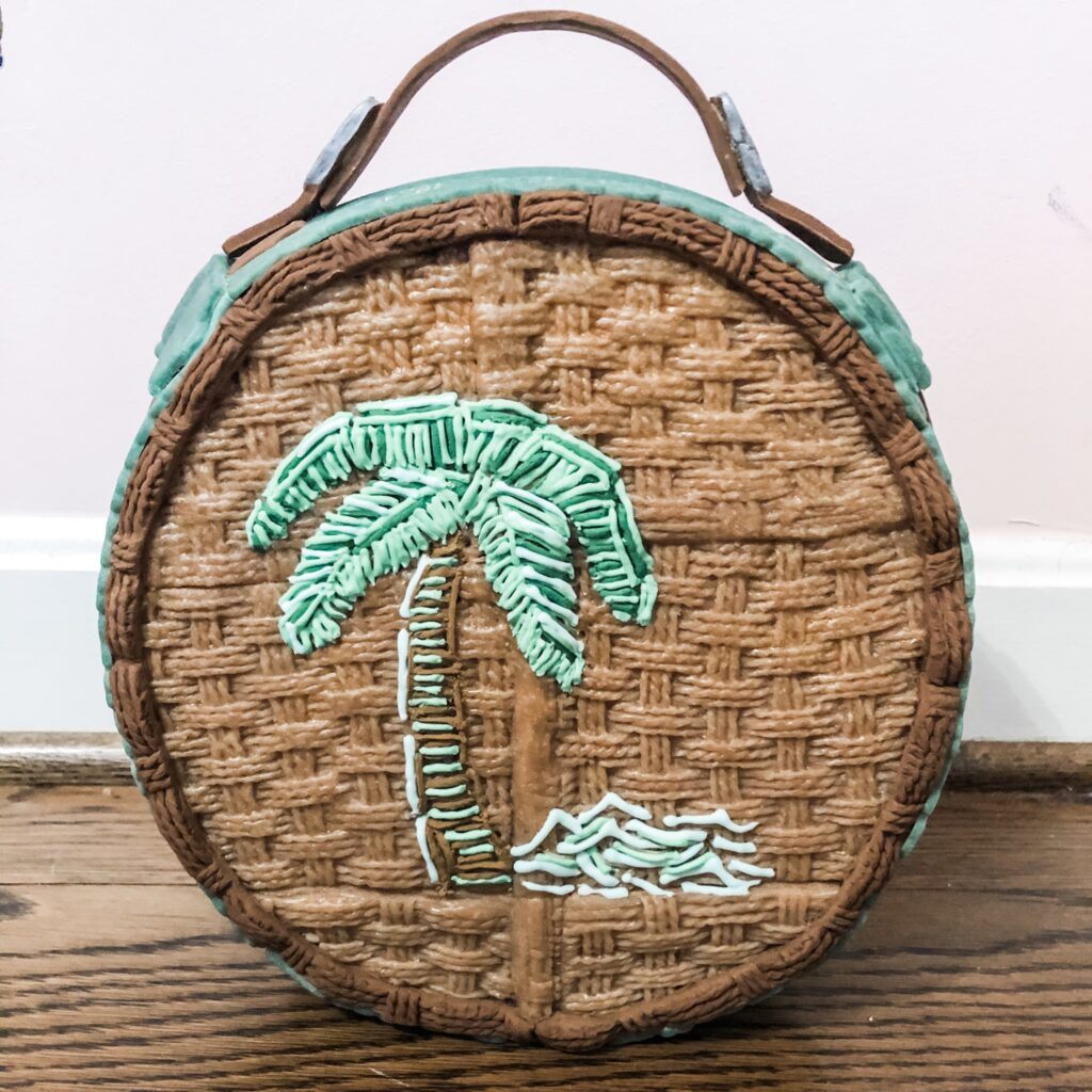 Round gingerbread rattan looking purse with a palmtree on it that looks embroidered.