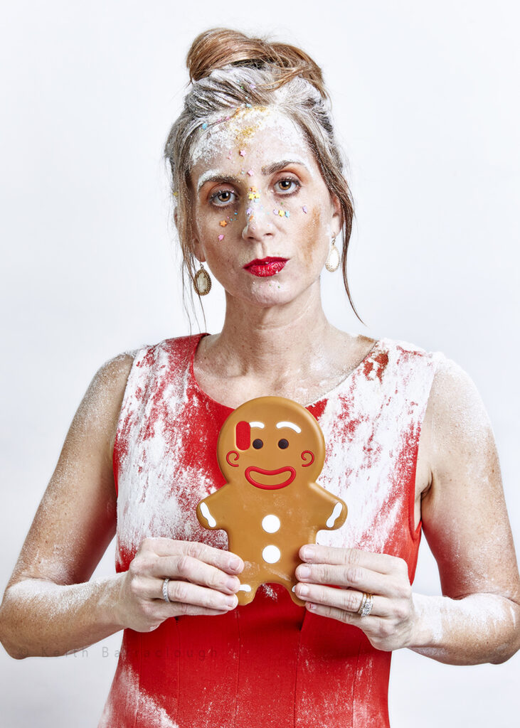 Lindsay Deibler, Ginger Gingerbread Lady, picture for The Redhead Project- holding a gingerbread man phone case with flour and sprinkles on her head.