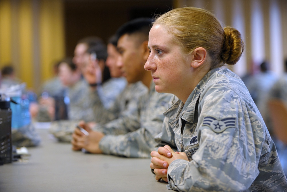 U.S. Air Force service members in uniform seated around table listening intently