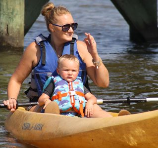Brooke Artesi on paddleboard with son Nicco, supervising campers