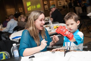 "A mother reacts to seeing her child make a fist with his new 3D printed fingers for the first time at the first e-NABLE ""Prosthetists Meets Printers"" conference at Johns Hopkins – Sept. 2014."