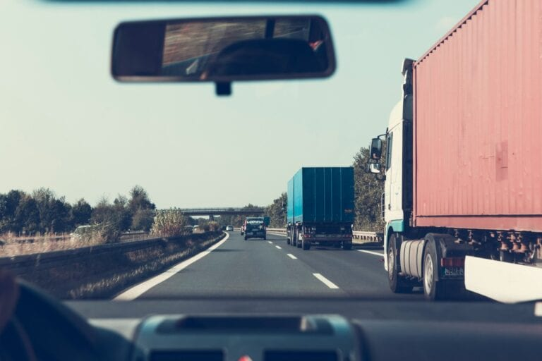 Canva Person Driving on Road Beside Trailer Trucks