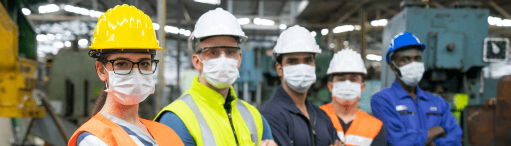 manufacturing operations employees with masks and PPE illustrating covid-19 challenges in the industry