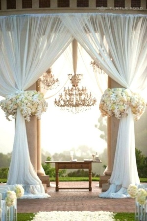 photo credit: unknown from Pinterest  We love this picture because it encompasses so many elements from Sean and Catherine's ceremony....chandeliers, roses and draping fabric.