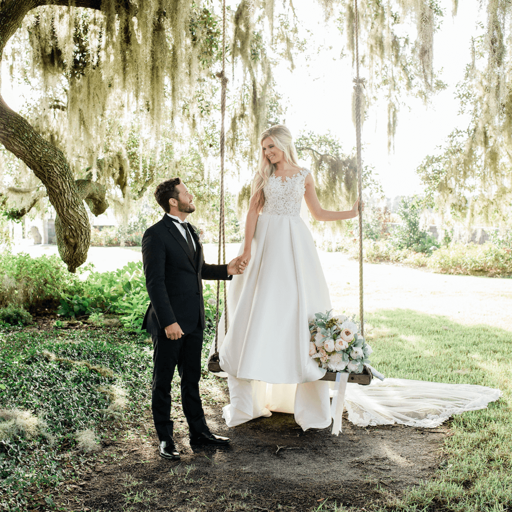 Groom stands on the ground next to his bride who is standing on a swing in her wedding dress. They're holding hands and Spanish moss hangs from a tall tree behind them. The whole photo is full of beautiful natural light.