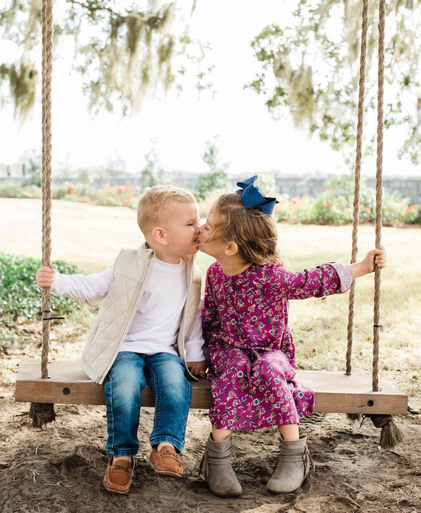 Two kids sit on a swing and kiss each other
