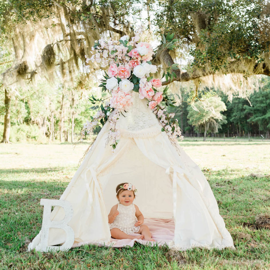 A baby girl wearing a floral headband sits in a white formal tent with flowers on top of it outside under a tree full of Spanish moss.