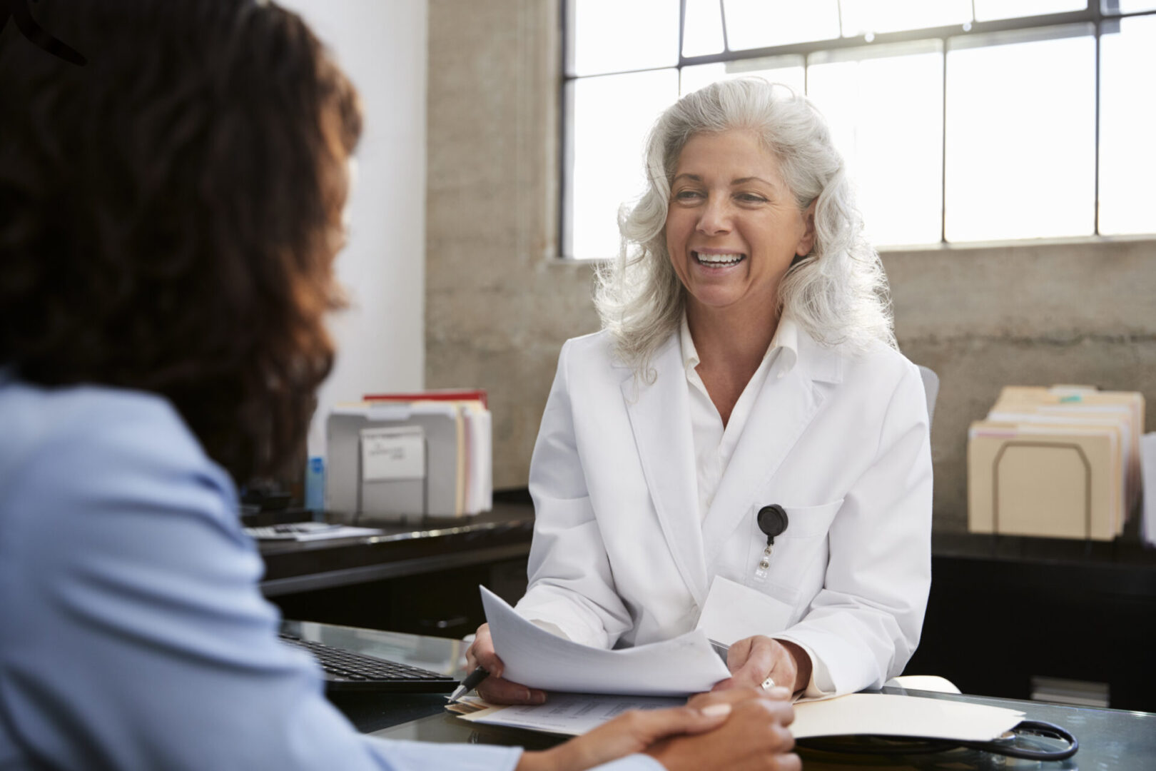 Smiling female doctor in consultation with patient in office