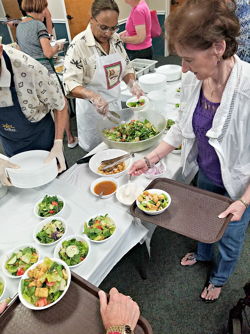 women and volunteers around a table getting salad