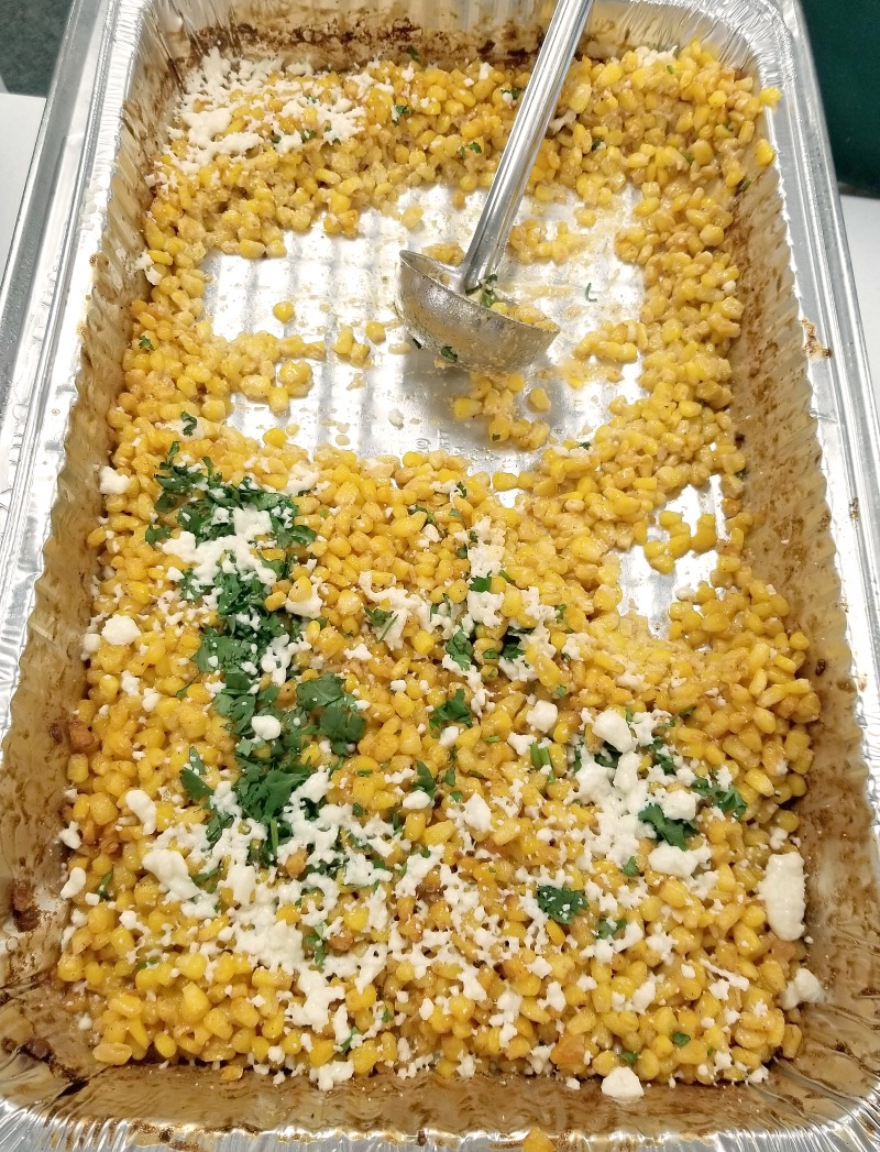 finished Mexican Street Corn in a hotel pan with a ladle for serving