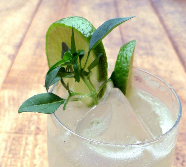 Cocktail of gin, lime and lemon juice with basil leaves