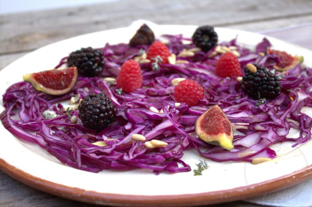 Red cabbage salad with red fruits and pine nut vinaigrette