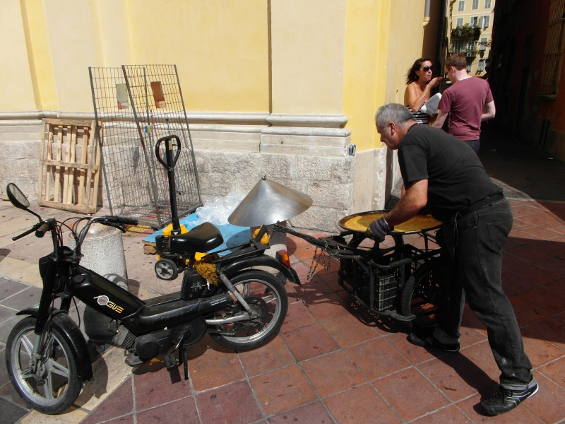 The socca is delivered by motorbike every few minutes to the food stand at the Flower Market on Cours Saleya in Nice