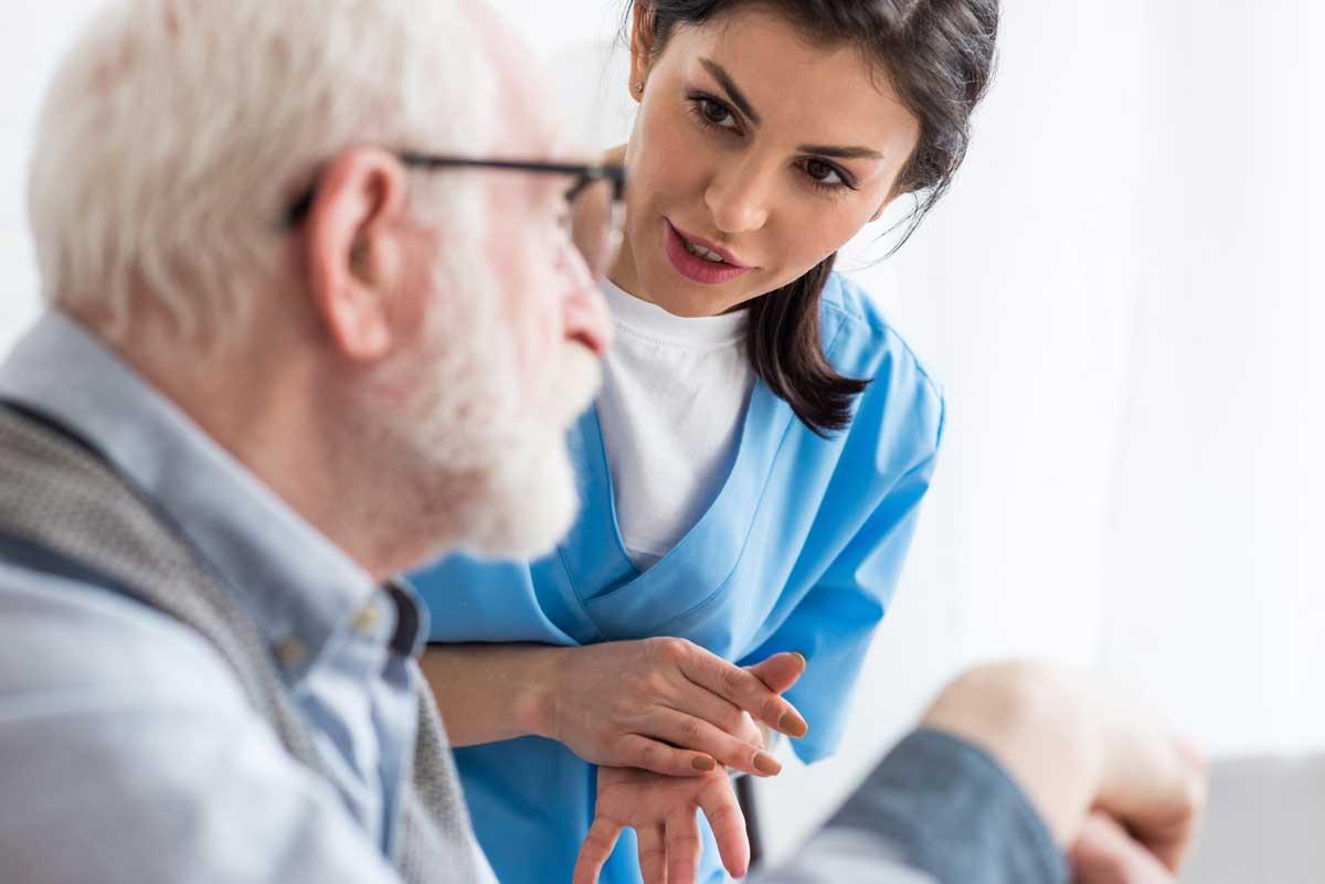 medical woman assisting elderly man