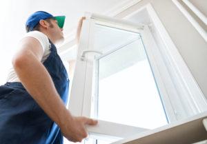 Professional handyman installing window at home