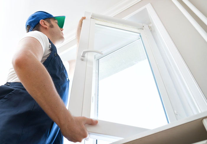 Professional handyman installing window at home