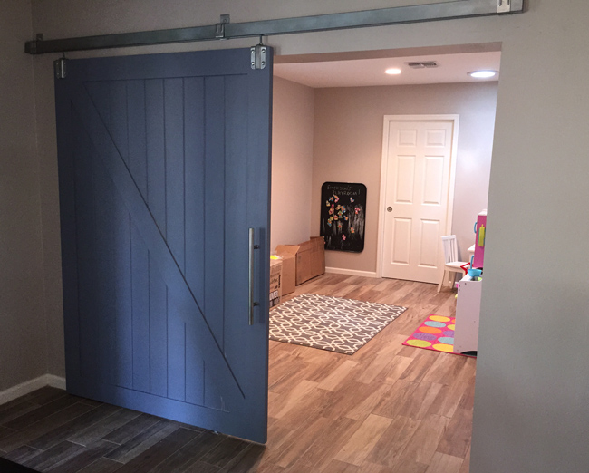 traditional ranch style barn door with box rail track painted blue