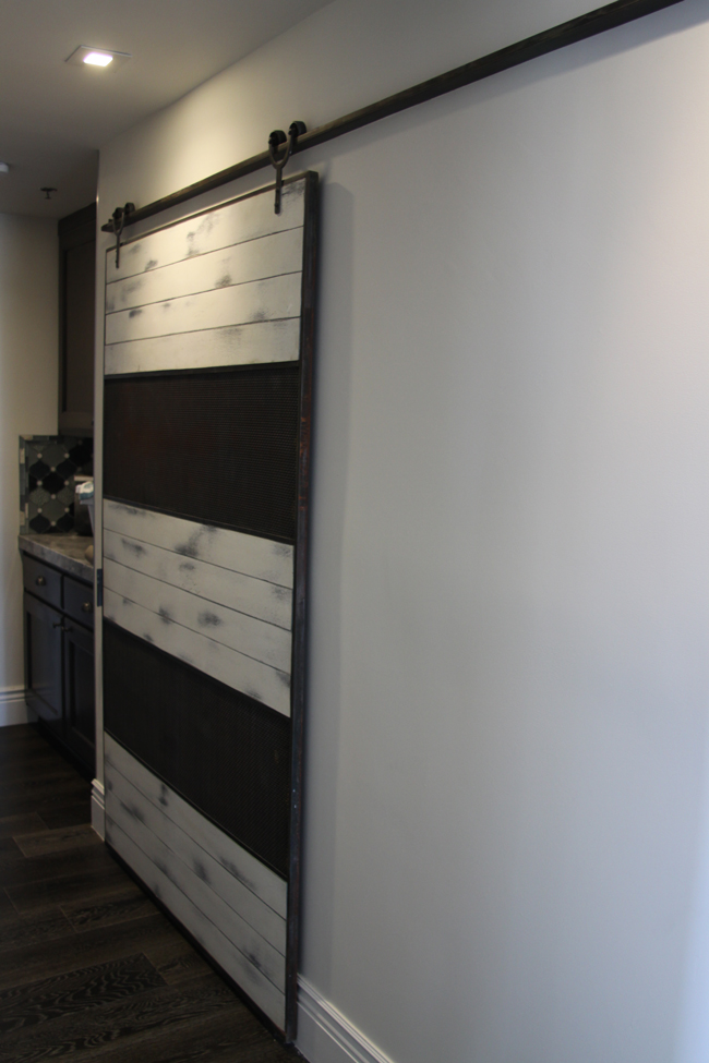 ranch style barn door with wire mesh and white weathered paint