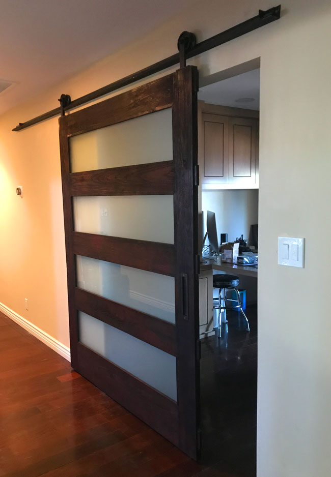 charred wood barn door with opaque glass panels