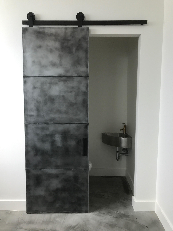 pure zinc panel barn door with an antique black patina finish