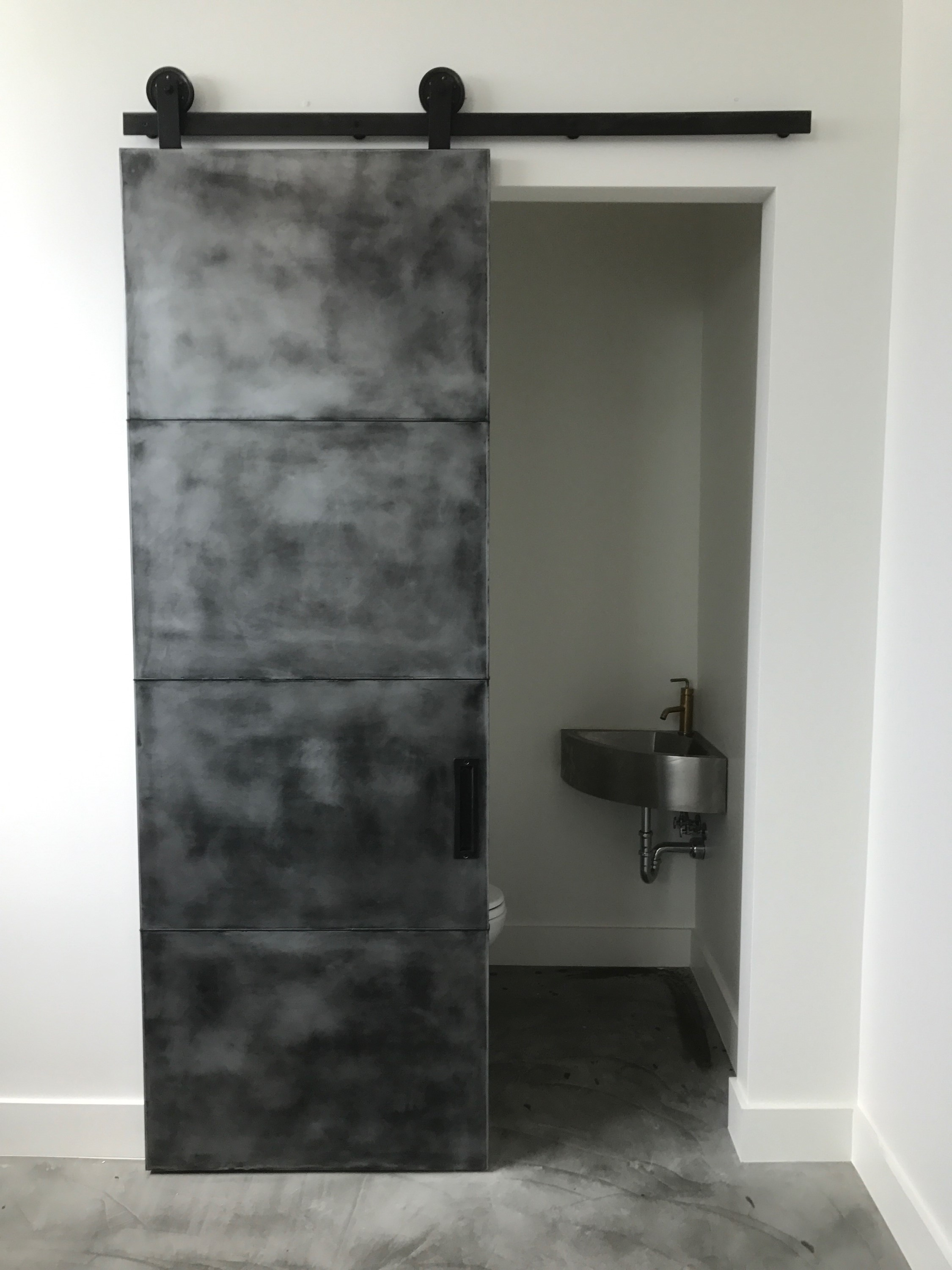 pure zinc panel barn door with an antique black patina finish
