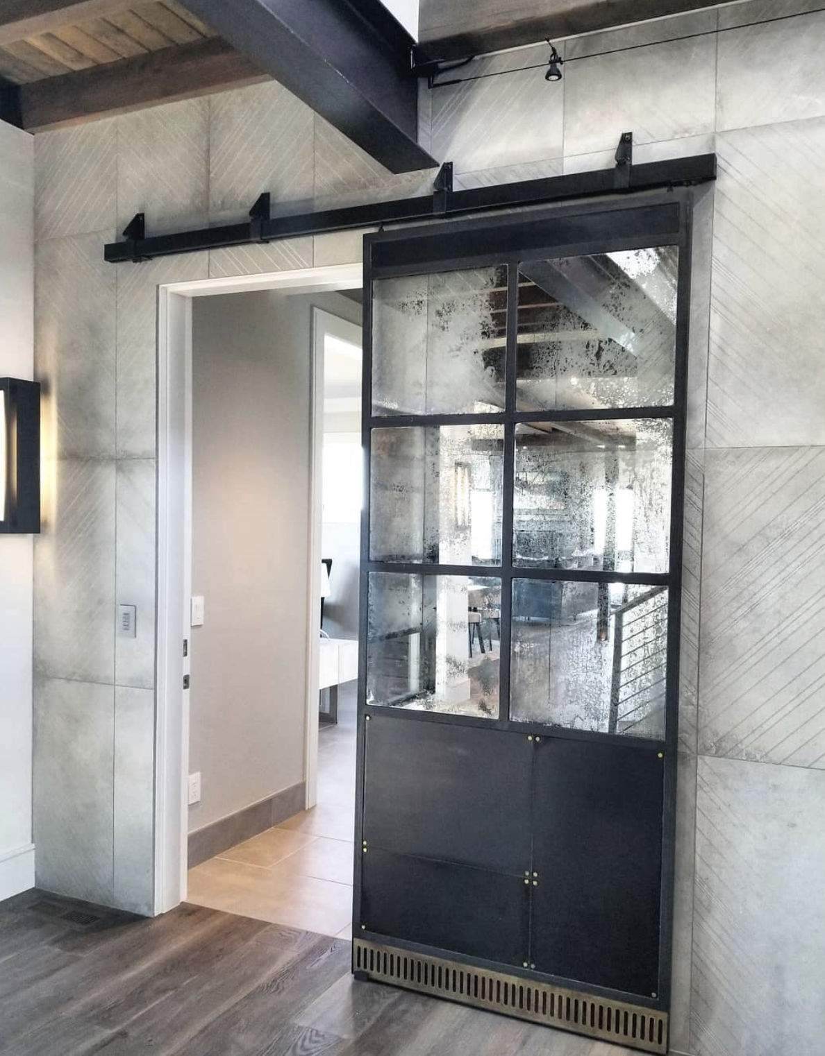 warehouse style barn door with antique mirrors and a metal panel tow kick with brass rivets and accent piece on the bottom