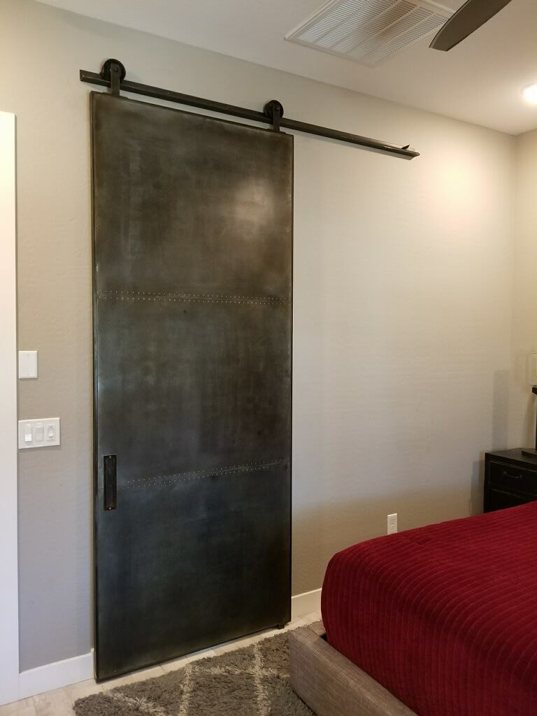 Steel panel barn door with rivets in the seams and patina finish