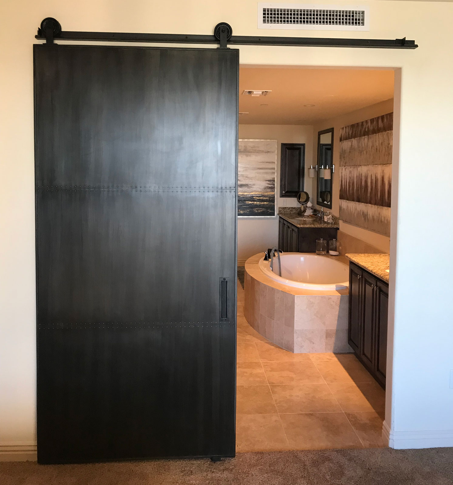 metal barn door with a patina finish and custom hardware