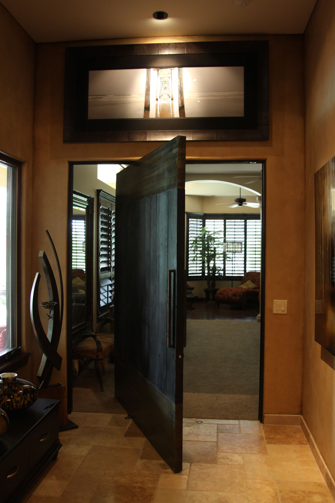 Shou Sugi Ban Pivoting door with patina steel