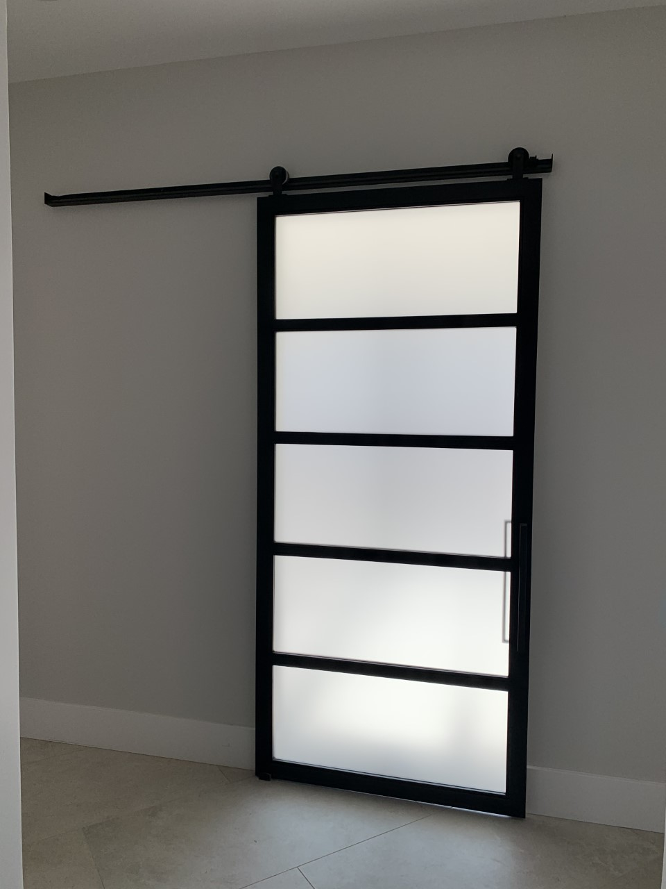 frosted glass and black metal barn door