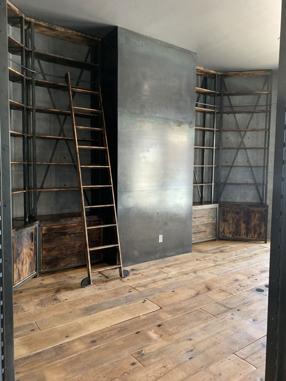 office library with steel and wood shelves and ladder