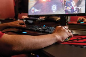 Close up of hands on mouse and keyboard - young person playinng esports