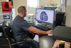 Technician creating 3D rendering of dentures on computer