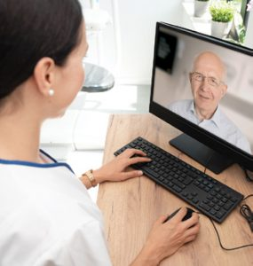 Nurse chatting with older man on computer