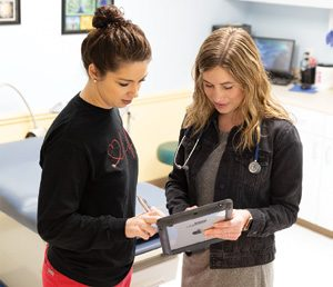 Nurses using tablet to check chart