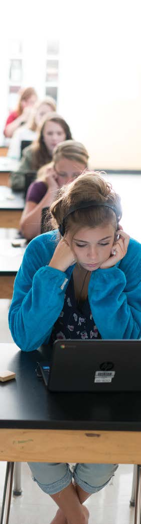 Students sitting at desks with headphones on listen to laptops