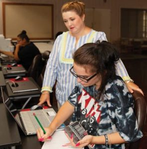 Julie Zuver looks on as Brianna Wood takes the GED assessment test.