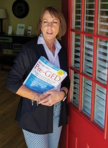 Mindy Wendele holder Pre-GED book while standing in door way