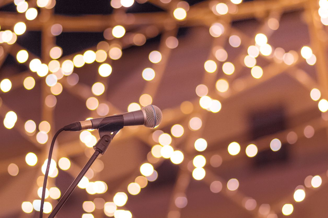 Microphone at a wedding with lighting strun throughout the reception getting ready for wedding speeches