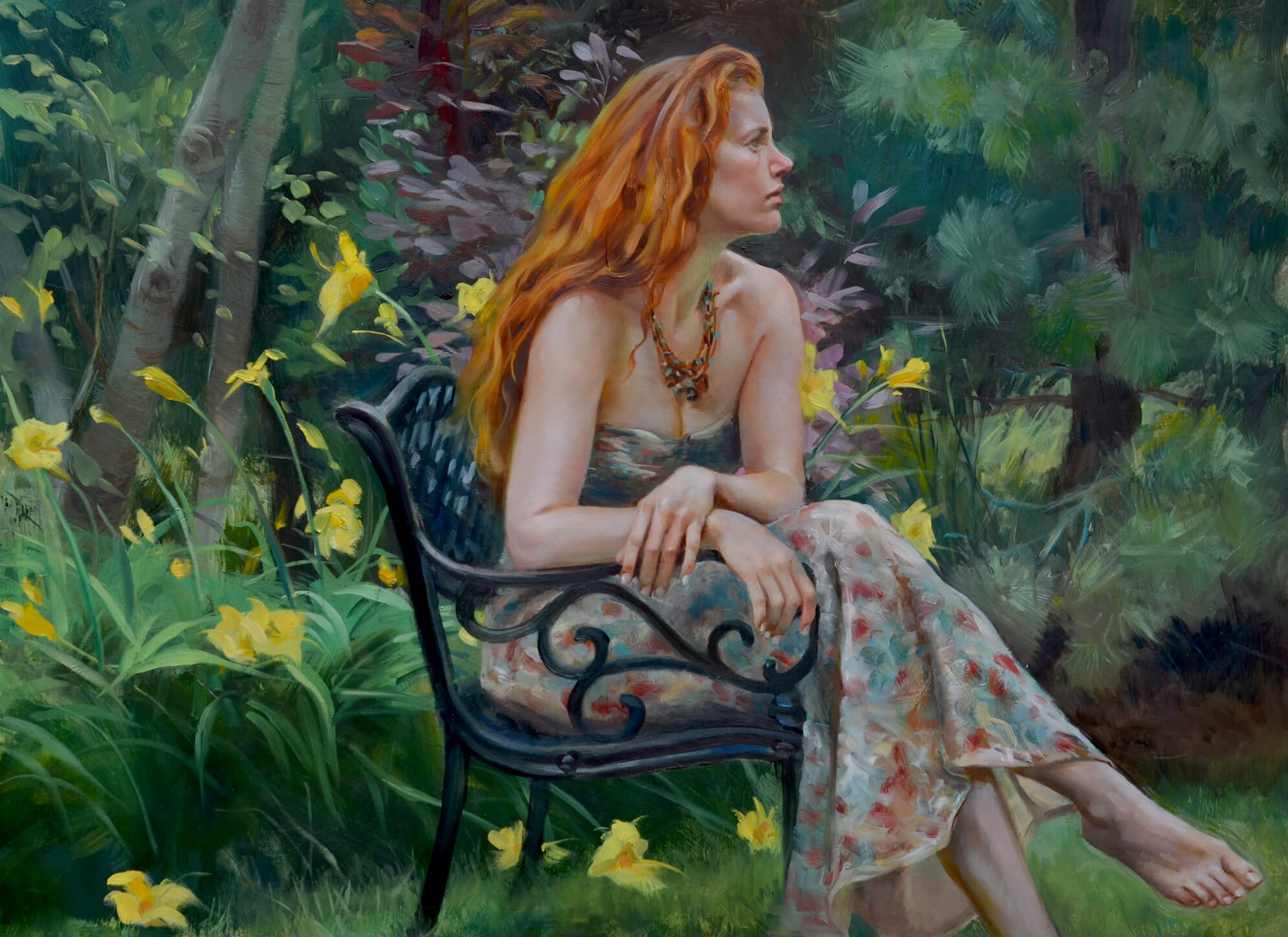 Young woman with red hair in a floral dress sitting on a wrought iron chair in a garden blooming with yellow lilies
